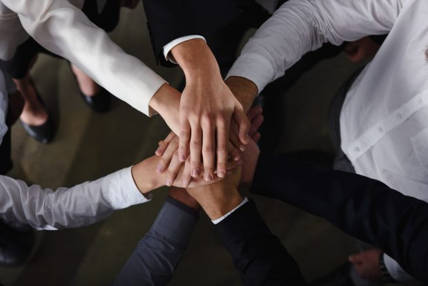 Business people joining hands in a circle in the office. concept of teamwork and partnership
