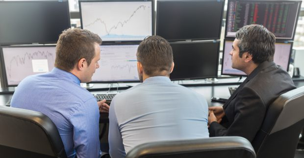 Businessmen looking at data on multiple computer screens in corporate office. Business people trading online. Business, entrepreneurship and team work concept.
