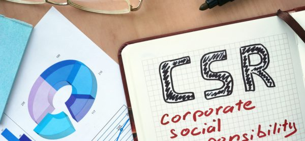 Notepad with words CSR corporate social responsibility concept and marker.