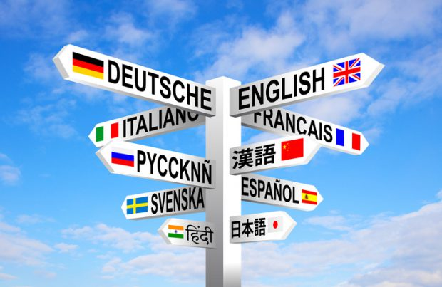 Multilingual languages and flags sign post against blue sky.