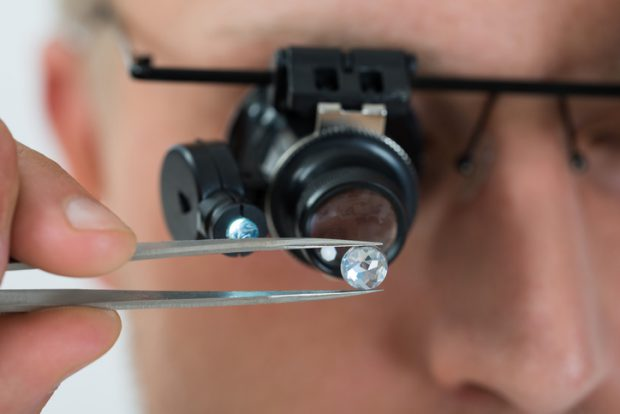 Close-up Of Person Looking At Diamond With Magnifying Loupe
