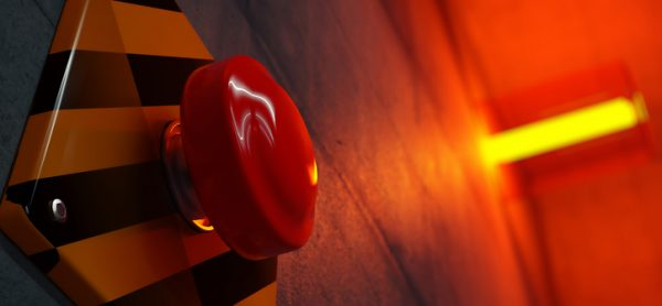 Close up of big red button during emergency situation. Red emergency light flashing in background.