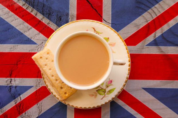 The Union Jack flag with a cup of tea served with a shortbread biscuit in a bone china cup and saucer