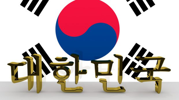 Korean hangul characters made of golden metal meaning South Korea in front of a korean flag.