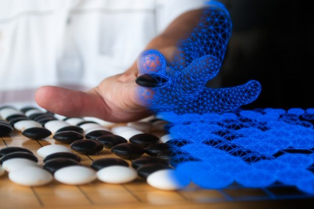 Human playing Go blended to blue computer  wireframe representing artificial intelligence concept.