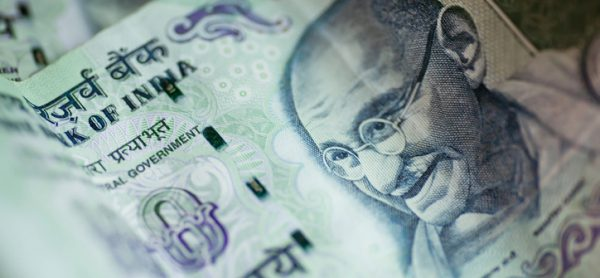 Banknotes of one hundred rupees. Selective focus on a portrait of Mahatma Gandhi on the official currency of the Republic of India