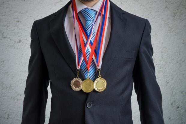 Awarded businessman is wearing many medals.