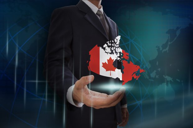 Businessman showing map of Canada on globe background