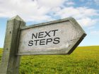 Wooden Next Steps Sign with Grass Background