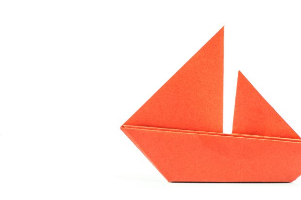 colorful paper origami boat or ship on white background