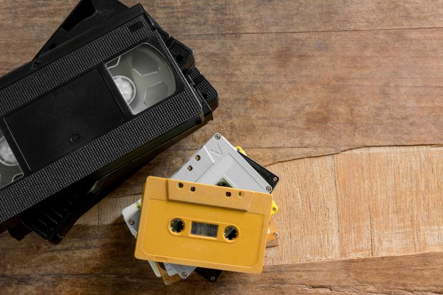 stack of old cassette and video tape on wooden board with copy space, top view. analog media technology concept.