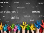 """Viele Kinderhände vor Wandtafel mit dem Wort """"Auf Wiedersehen"""" in vielen Sprachen"""