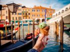 Hand man holds an Italian ice cream on background of Grand Canal and Handol in Venice, Italy. Concept tourism.